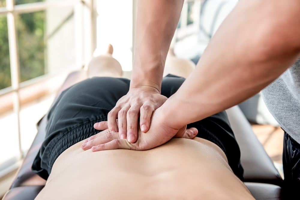 a physiotherapist reduces lower back pain for a man
