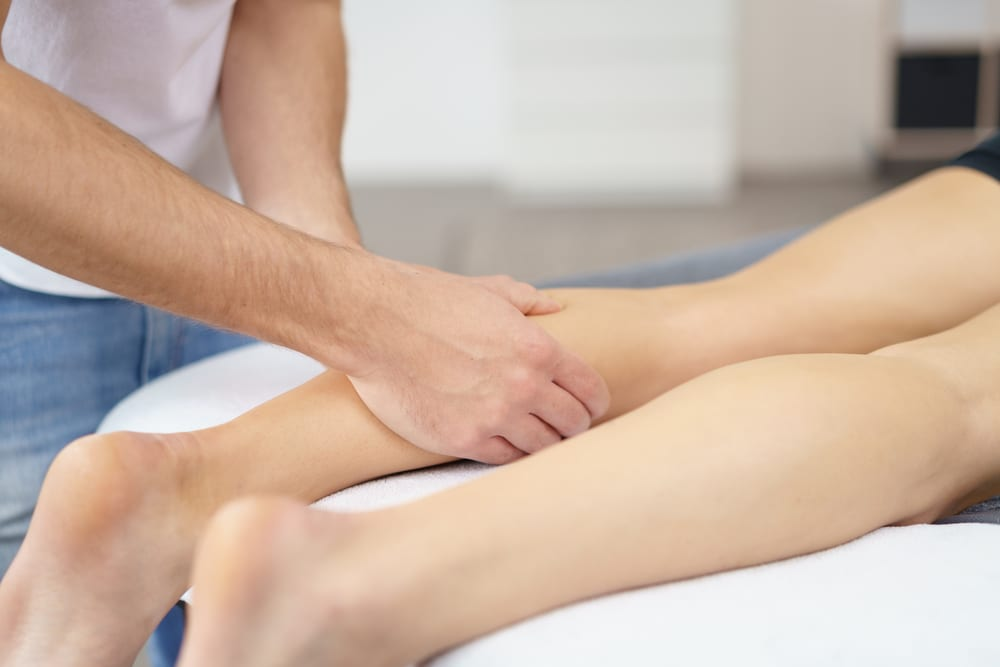 a physiotherapist checks calf strain for a client