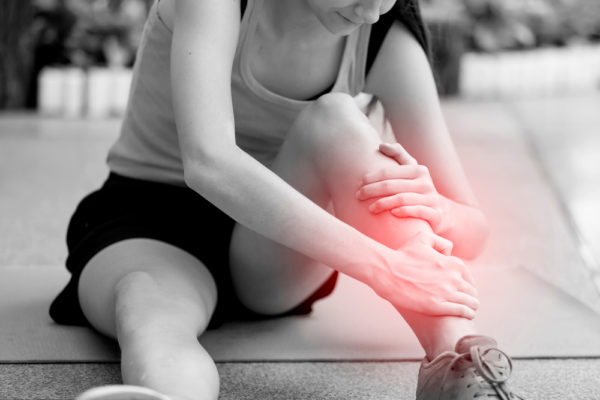 a woman suffering from shin pain while doing exercises