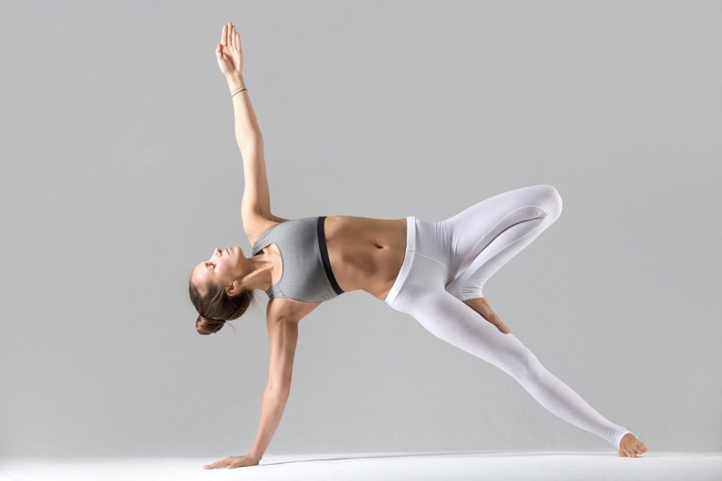 young woman practicing yoga stretching in side plank exercise